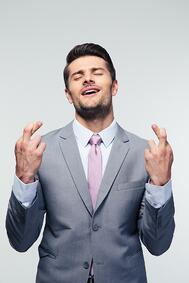 Handsome businessman with fingers crossed over gray background.jpeg