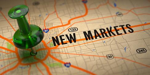 New Markets Concept - Green Pushpin on a Map Background with Selective Focus..jpeg