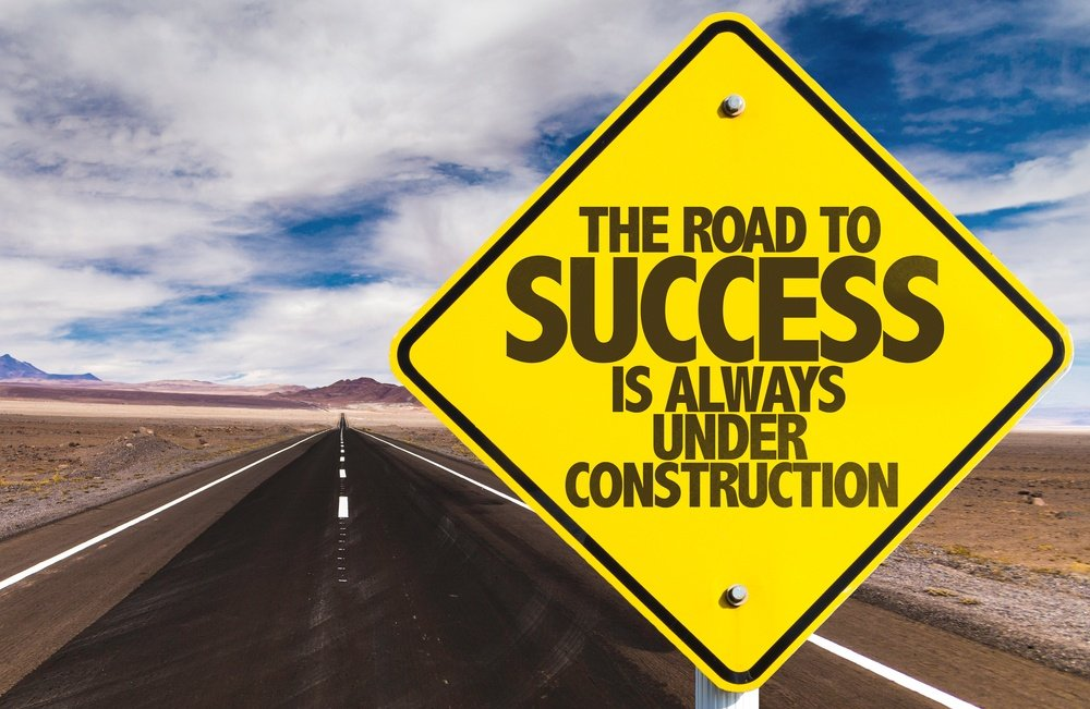 The Road to Success is Always Under Construction sign on desert road.jpeg